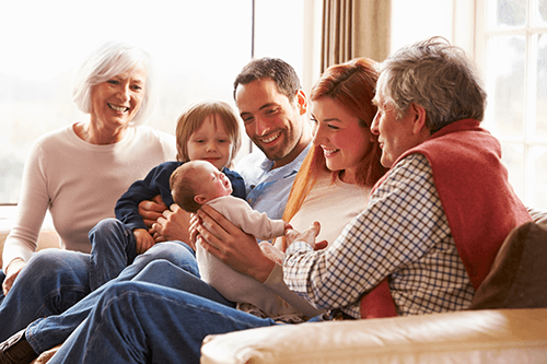 happy family with grandparents holding newborn
