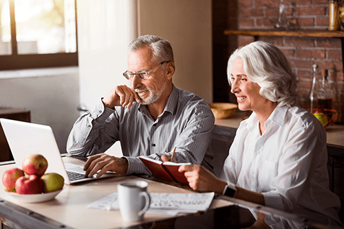 senior adult couple looking at laptop