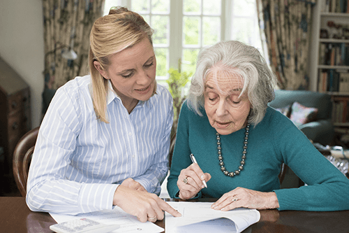 adult daughter helping her senior mother with paperwork