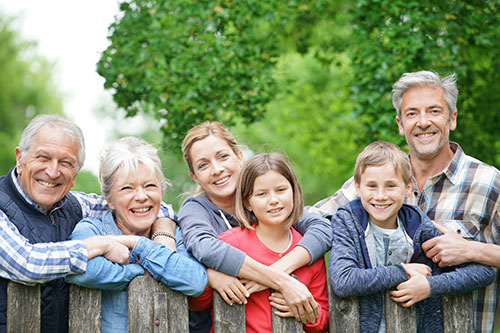 happy family with grandparents smiling at camera
